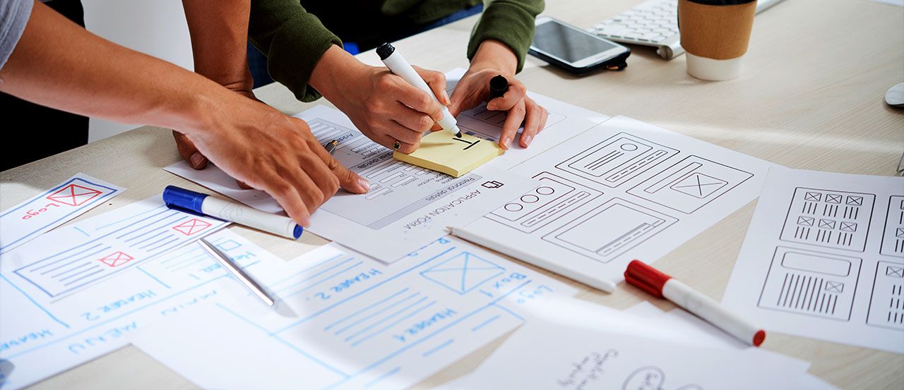 Hands of two designers working on sheets of wireframes and adding notes on post it note during a design workshop