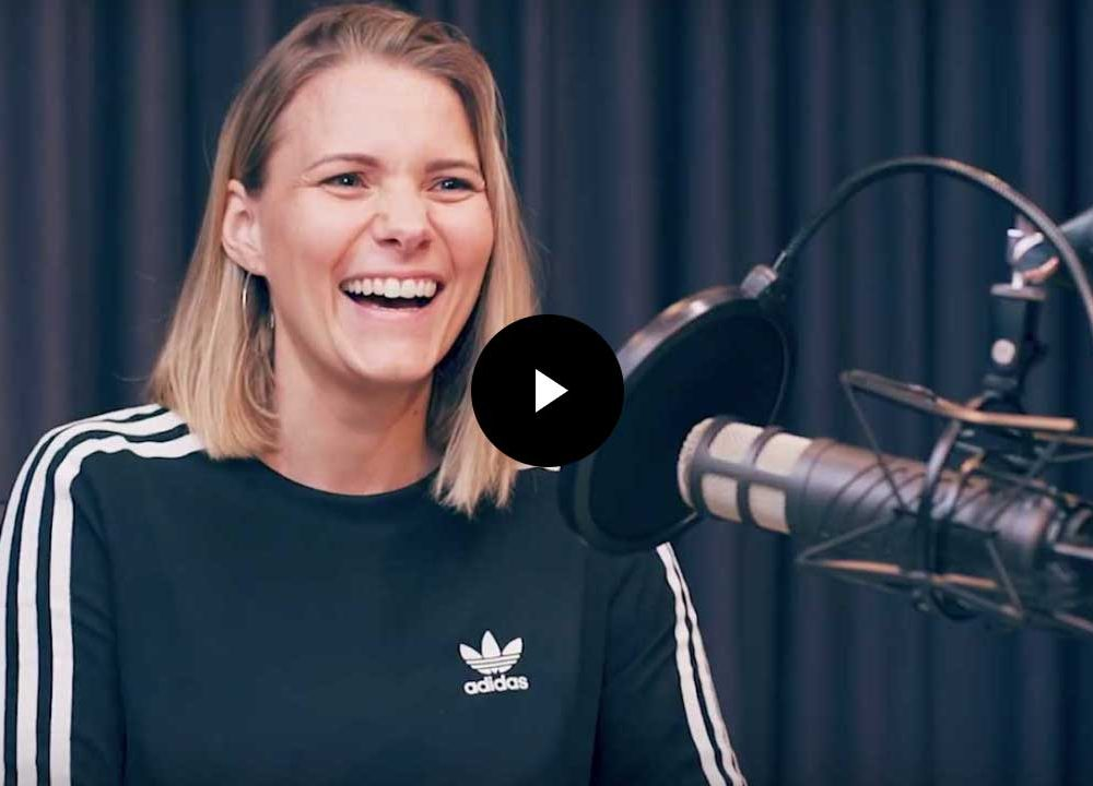 Jana Dowling founder of Arkeo sitting in a podcast studio with a microphone in front of her