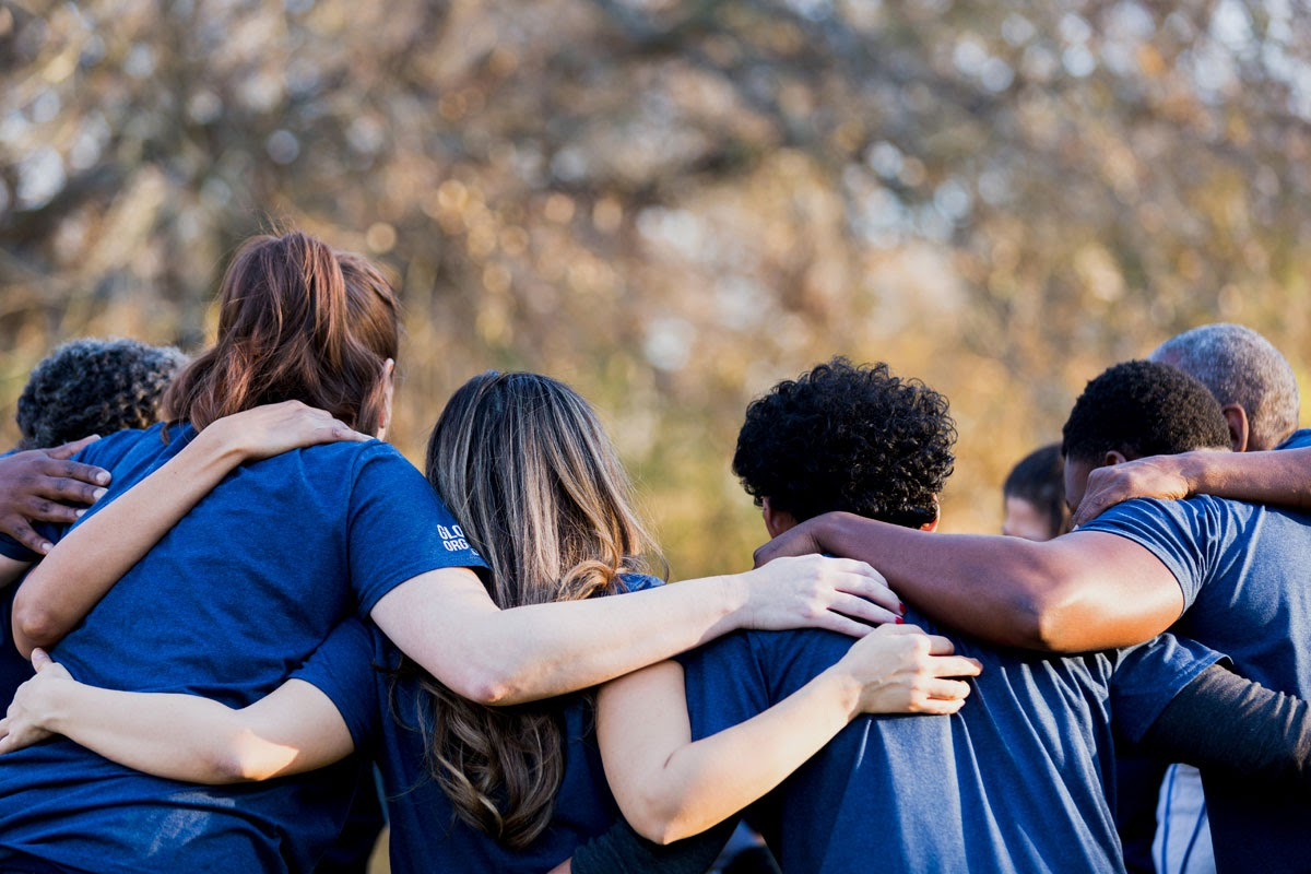 Group of digital creatives standing in a circle with their arms around each others shoulders