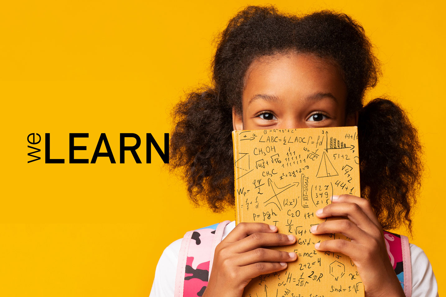 Pupil with curly hair holding a notebook with maths equations on it in front of her nose and mouth, and welearn logo