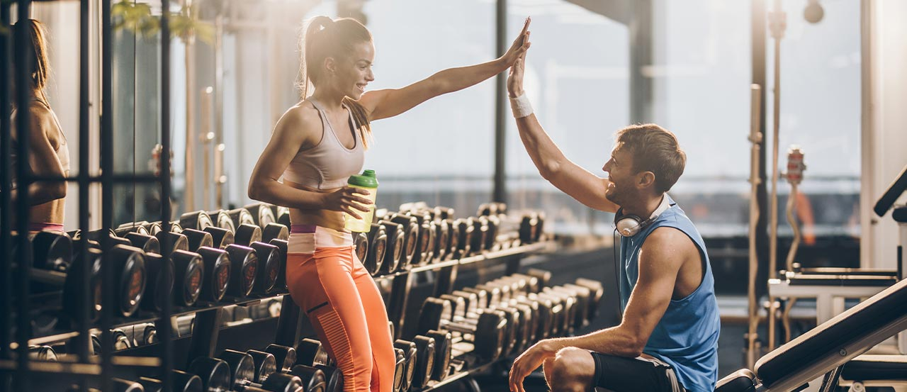 A women standing in front of dumbbells in a gym giving a high-five to a man sitting