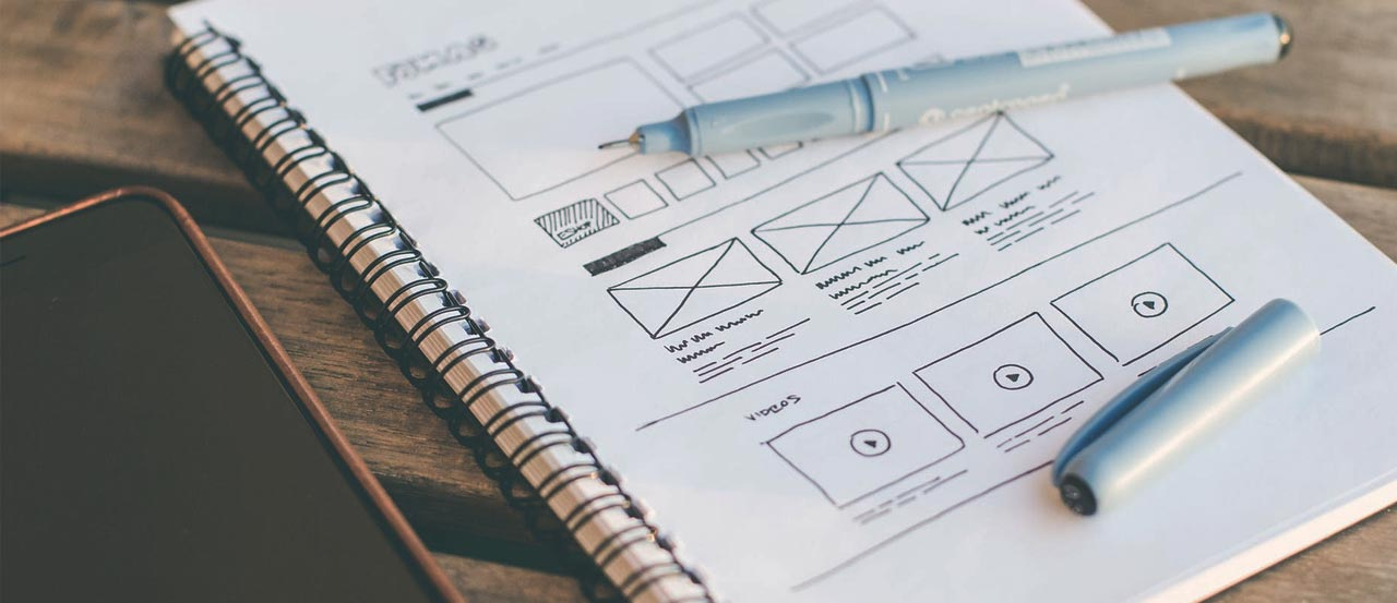 Open notepad with UX wireframes and a pen