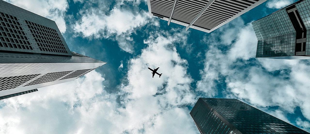 Plane in the sky between skyscrapers