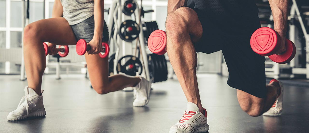 A woman and a man doing lunges with dumbbells in hands