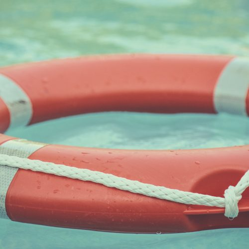 red lifebuoy with white ropes in water