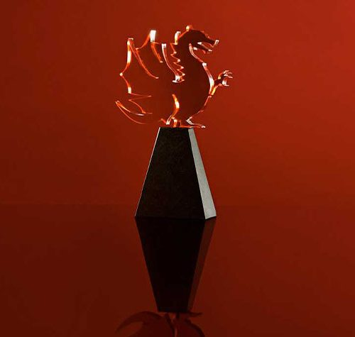 A glass dragon award on a red background