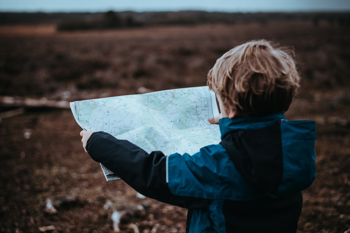 a boy looking at the map looking for navigation
